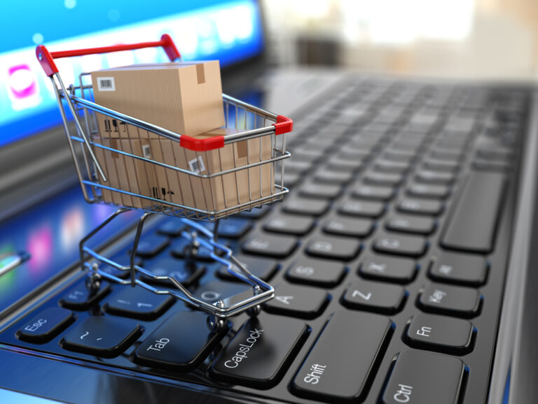 miniature shopping cart on top of computer keyboard