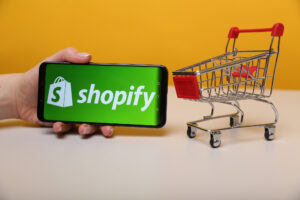 Shopify logo on smartphone beside miniature shopping cart