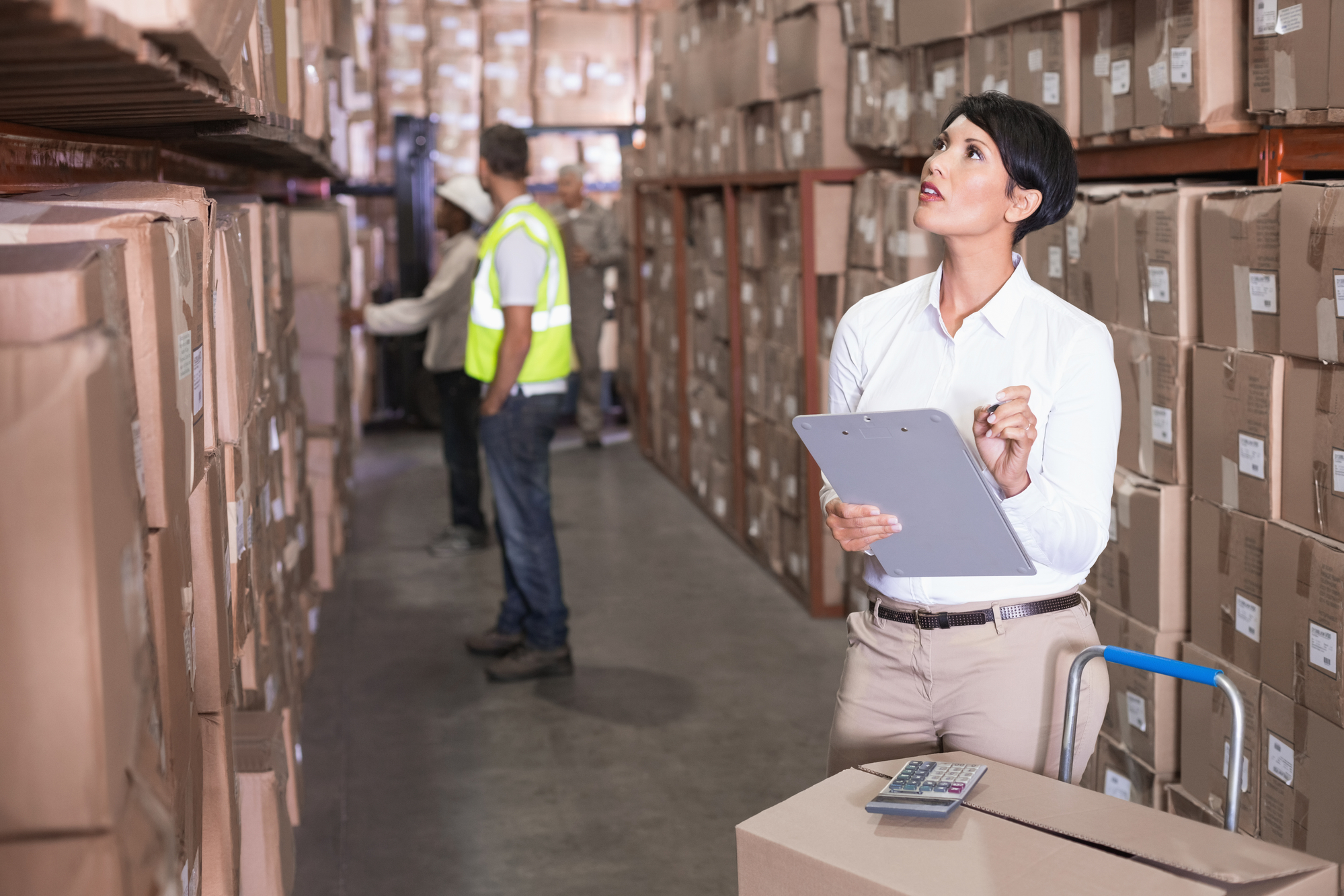 woman in warehouse inspecting inventory