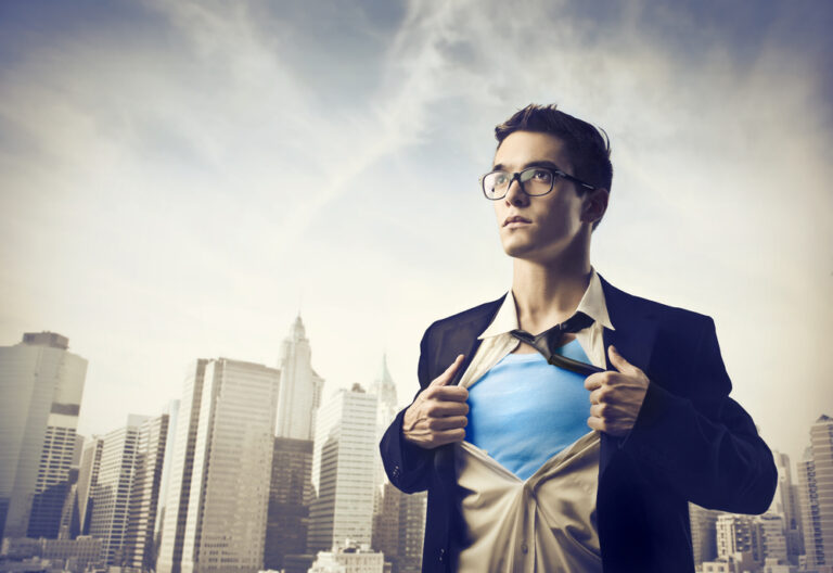 Young businessman showing the superhero suit under his shirt with cityscape in the background